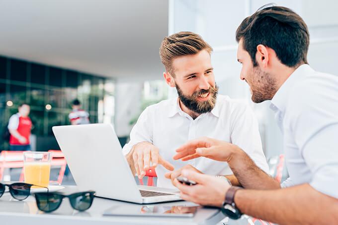 Deux jeunes hommes d'affaire qui parlent d'un projet dans un Café