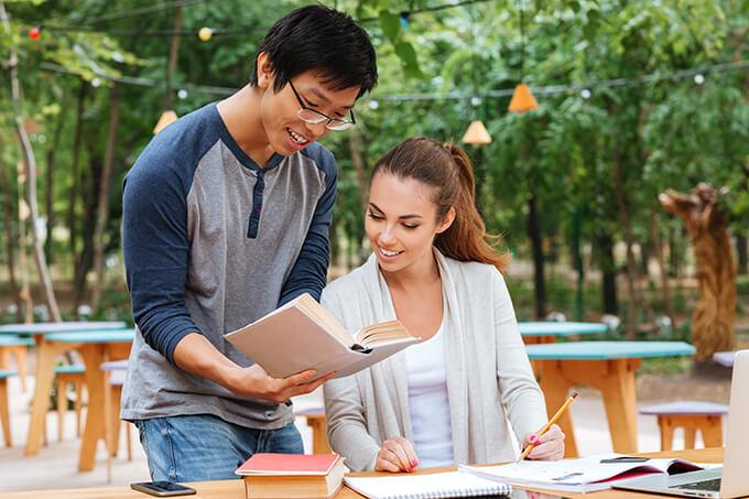 Jeune homme asiatique enseigne a une jolie femme un article