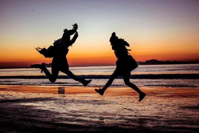 deux personnes qui sautent sur la plage